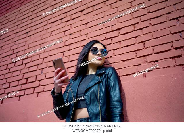 Portrait of young woman with smartphone wearing sunglasses and black leather jacket