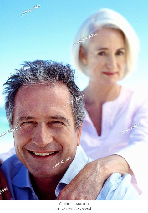Portrait of a middle aged woman giving her boyfriend a shoulder massage