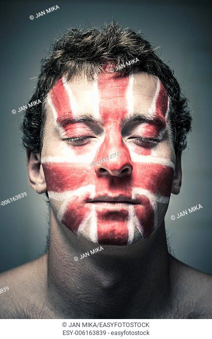 Portrait of man with British flag painted on his face and closed eyes
