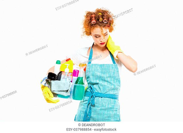 Exhausted young woman in curlers and yellow gloves holding plastic box with cleaning supplies and having neck pain over white background