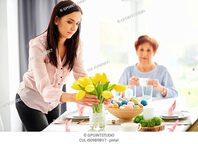 Mid adult woman arranging yellow tulips at easter dining table