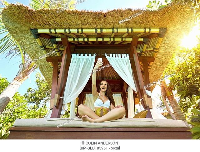 Pacific Islander woman taking cell phone selfie in cabana