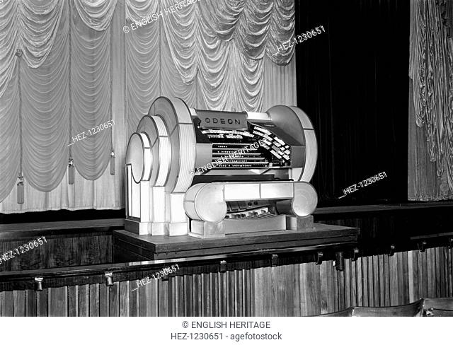 Organ console in the auditorium at the Odeon, Leicester Square, London, 1937. Bearing the Odeon logo, the Art Deco organ reflects the contemporary style of the...