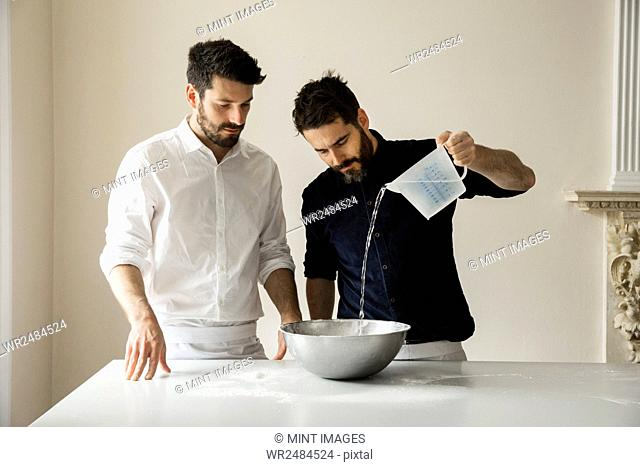 Two bakers standing at a table, preparing bread dough, pouring water from a measuring jug into a metal mixing bowl