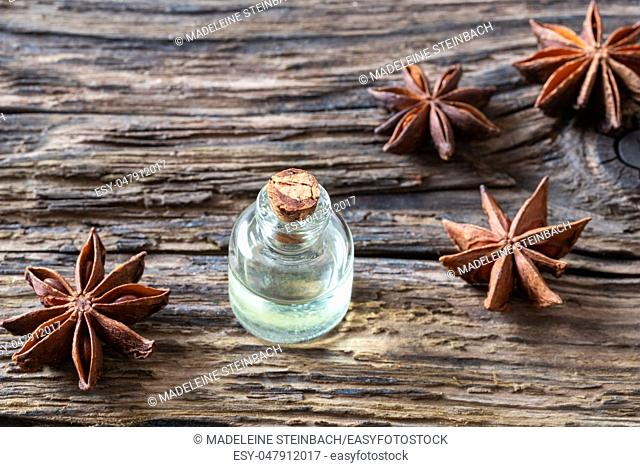A bottle of essential oil with star anise on a rustic background