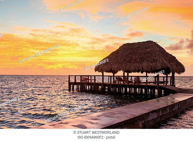 Stilted waterfront pier and thatched roof at sunset, St. Georges Caye, Belize, Central America