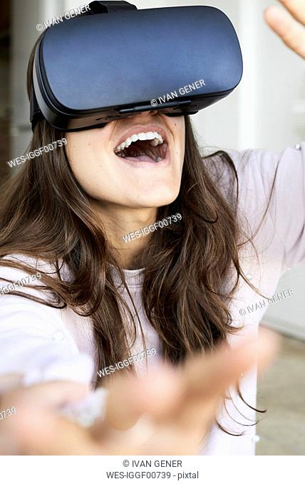 Young woman having fun using virtual reality headsets at home