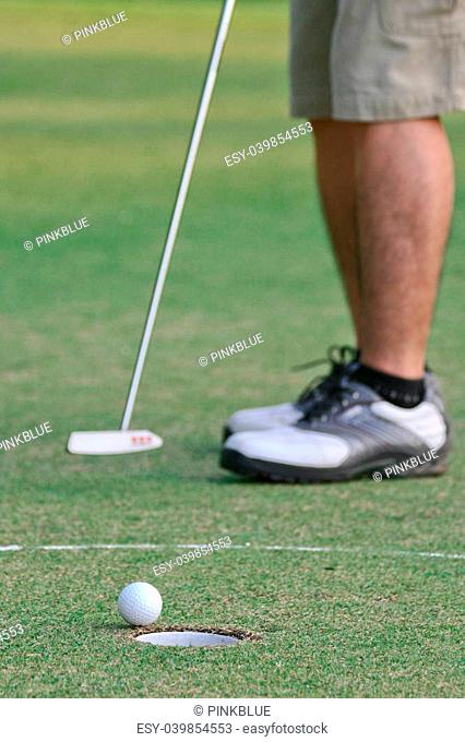 A man putts a golf ball to the hole