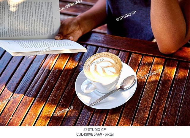 Young woman sitting outdoors, reading book, coffee in front of her, mid section