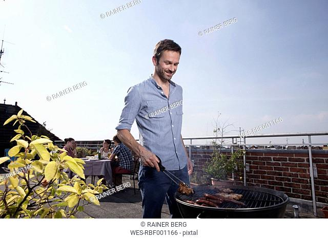 Germany, Berlin, Man barbecueing on grill, smiling