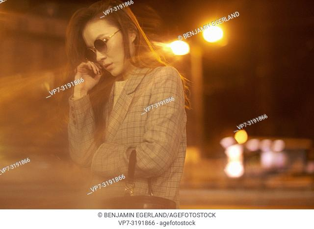 Fashionable woman on the street by night. Munich, Bavaria, Germany