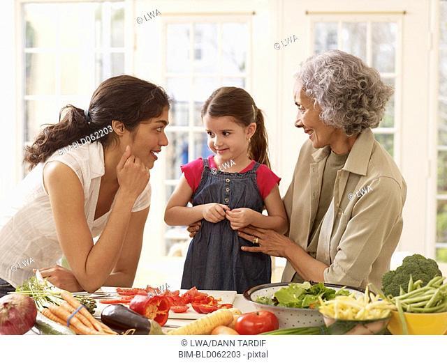 Multi-generational Hispanic family cooking in kitchen