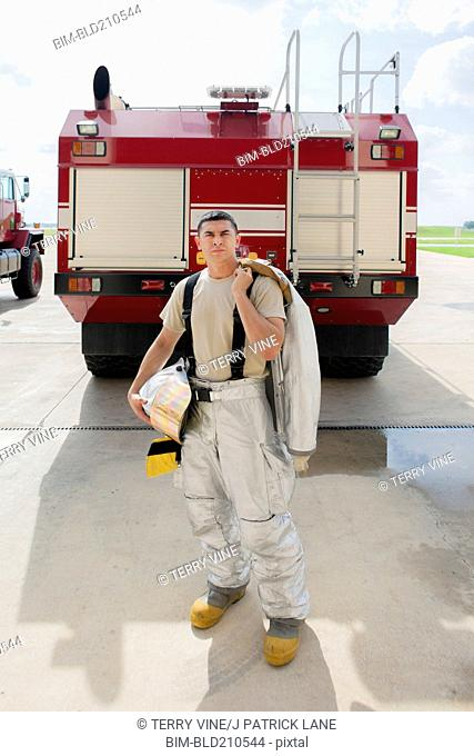 Mixed race firefighter standing by fire truck