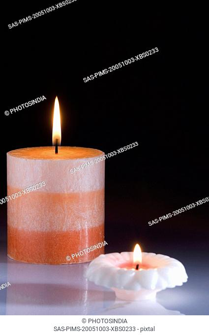 Close-up of two colorful candles burning