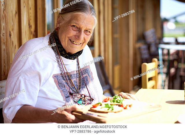 happy senior woman eating healthy bread with vegetables