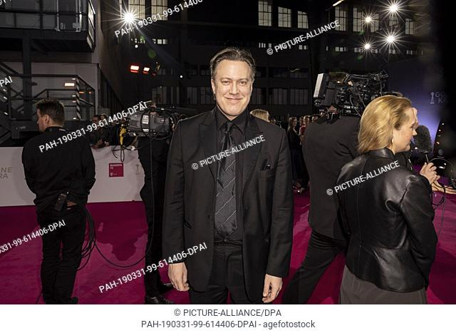 30 March 2019, Berlin: Nicholas Ofczarek, actor, stands on the red carpet in front of the Golden Camera award ceremony in Berlin's disused Tempelhof Airport