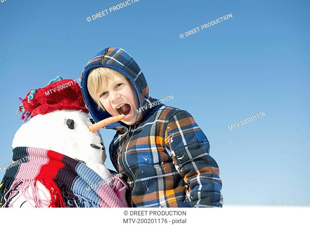 Boy standing with snowman, mouth open, Bavaria, Germany