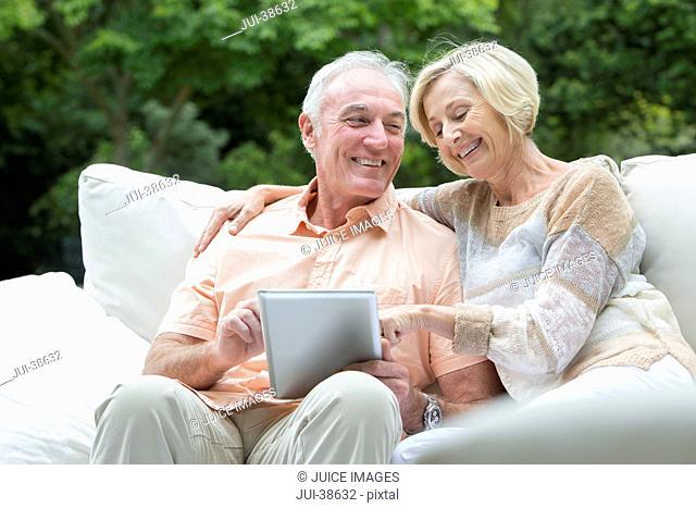 Senior couple using digital tablet on outdoor sofa