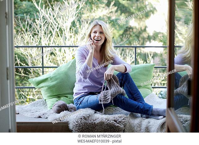 Blond woman sitting on balcony telephoning