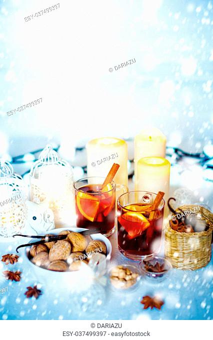 Light Christmas Decorations with Drawn Snow for Festive Mood. Two Glasses with Mulled Wine, White Candles and Lantern, Toy Owl, Walnuts and Spices