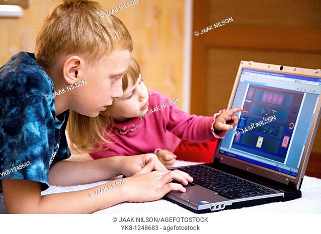 Teenage Boy with Kid Girl Lying Down and Using Laptop Computer