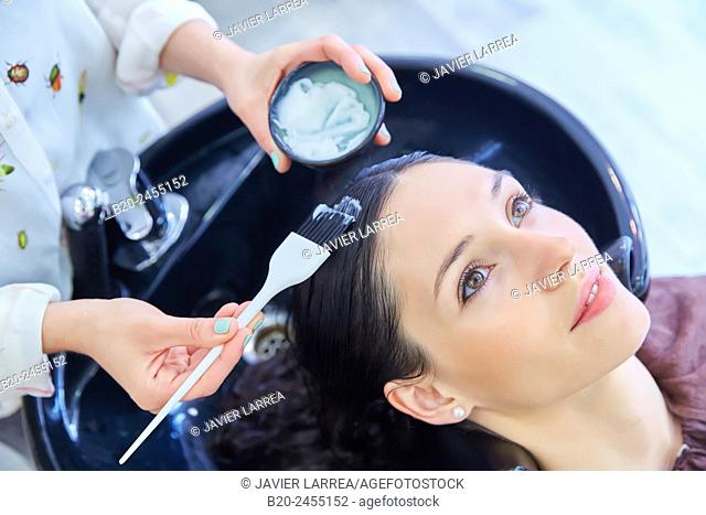 Hairdresser applying hair conditioner to customer's hair. Hairdressing salon and Beauty Clinic