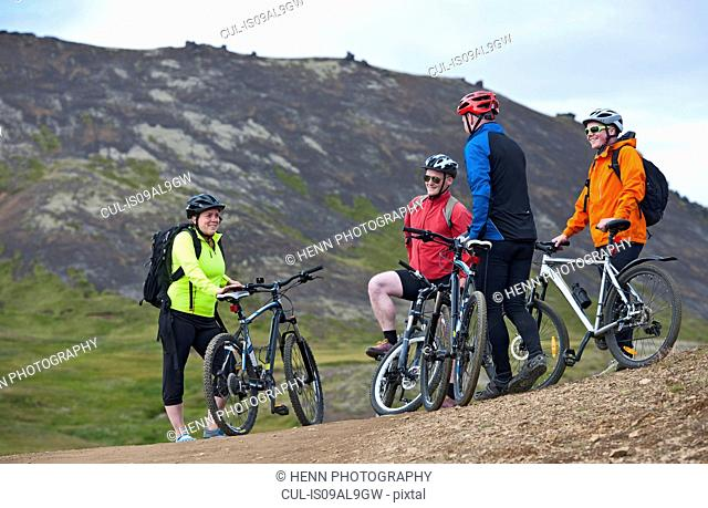 Four mountain bikers taking a break, Reykjadalur valley, South West Iceland