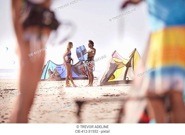 People with kiteboarding equipment talking on sunny beach