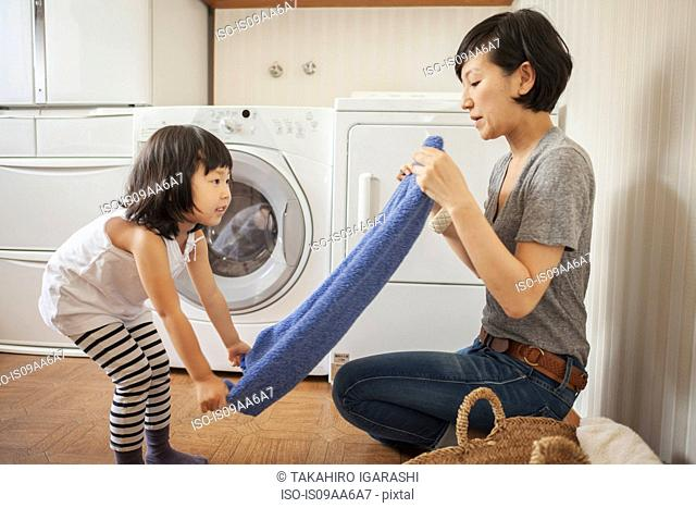 Mother and daughter folding towel