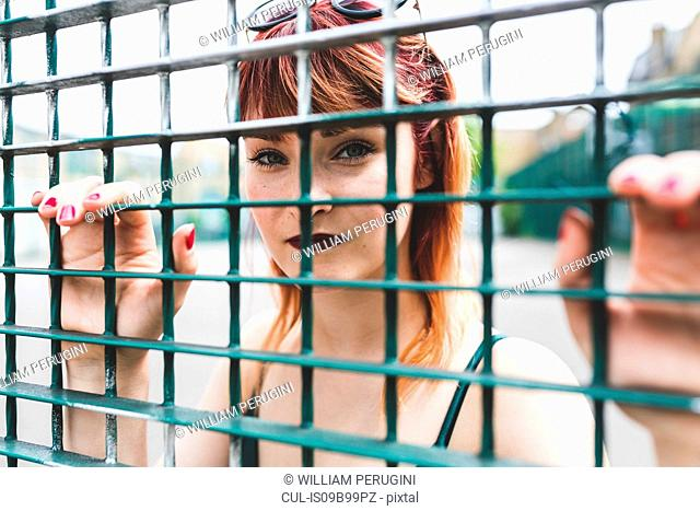 Portrait of young woman with dip dyed hair behind wire fence