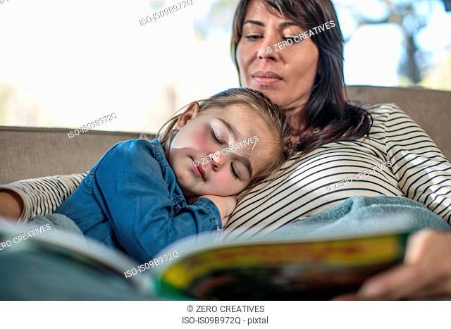 Girl sleeping with mother on sofa