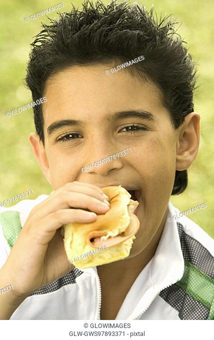Close-up of a boy eating a burger