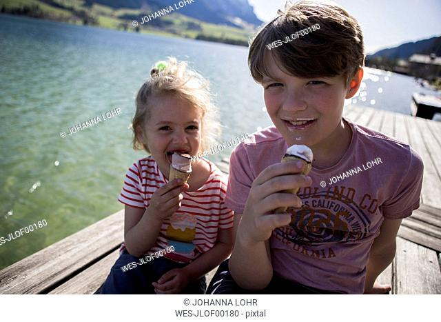 Austria, Tyrol, Walchsee, portrait of brother and sister sitting on jetty at a lake eating ice cream cones