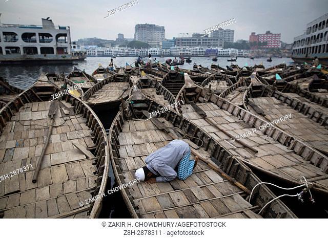 DHAKA, BANGLADESH - MAY 30 : Boatman pray Asr prayer on his boat during Ramadan prayer in Buriganga river in Dhaka, Bangladesh on May 30, 2017