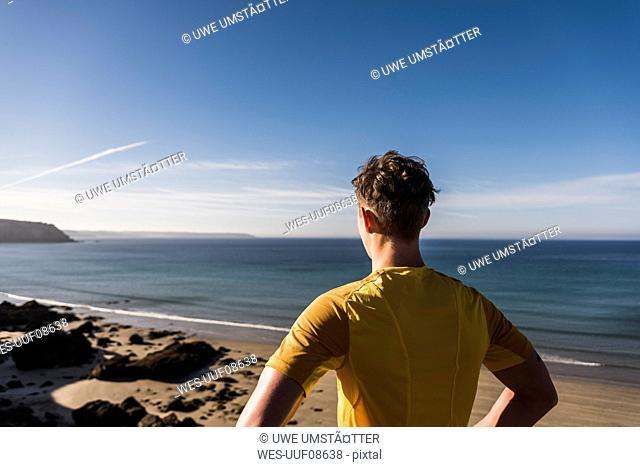 France, Crozon peninsula, sportive young man at the coast looking at view
