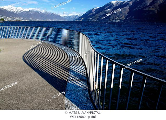 Banister with shadow with view over an alpine lake with snow-capped mountains