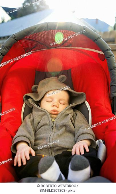 Caucasian baby sleeping in car seat