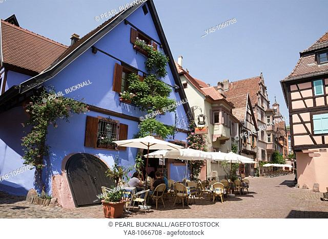 Riquewihr, Alsace, Haut-Rhin, France, Europe  A la Couronne restaurant in old building on narrow cobbled street with people dining outside in picturesque...