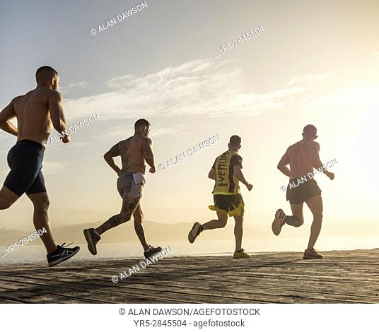 El Confital, Las Palmas, Gran Canaria, Canary Islands, Spain. Muscular young men from local boxing club running along beach boardwalk at sunset
