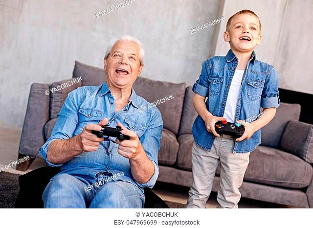 Two kids. Humorous energetic excited man and his grandson enjoying the play while using special controllers and looking excited