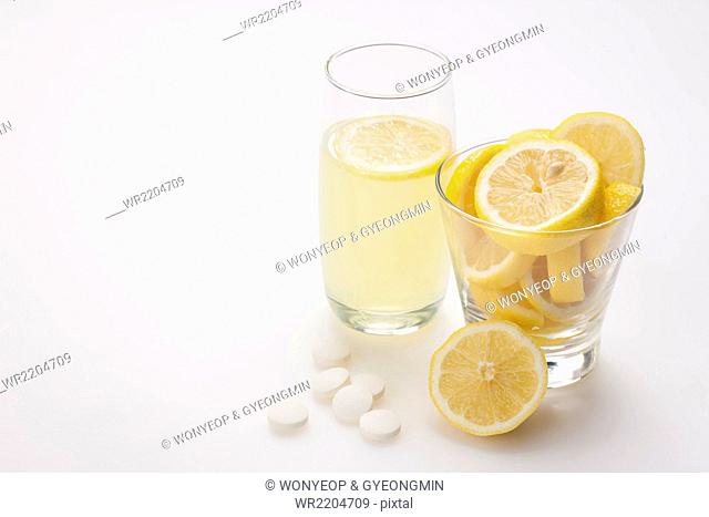 Glass of lemonade with a lemon slice in it and slices of lemon in another glass and vitamin pills placed with them