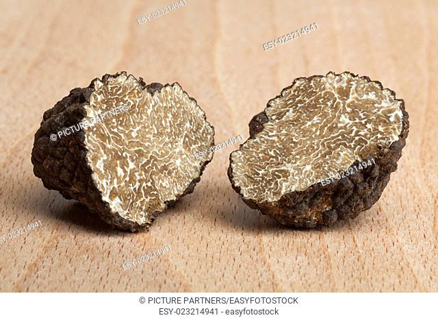 Two fresh half black truffles on wood
