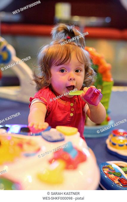 Baby girl playing with toys in a playroom of cruise liner