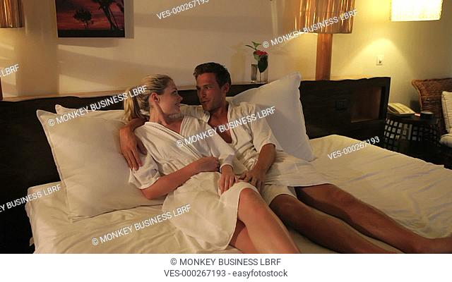 Couple wearing bathrobes lying on hotel bed and talking.Shot on Canon 5d Mk2 with a frame rate of 30fps