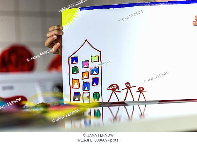 Girl holding finished drawing of house and familiy