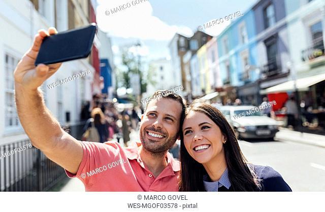 UK, London, Portobello Road, happy couple taking selfie with cell phone