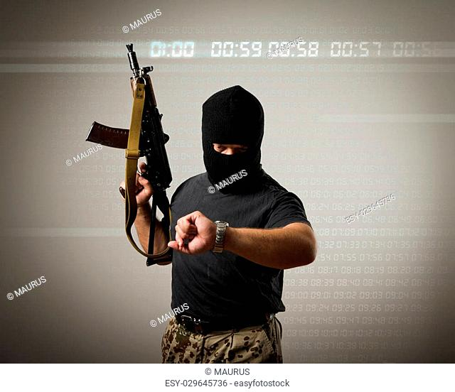 Terrorist with gun looking at his wristwatch. Time concept