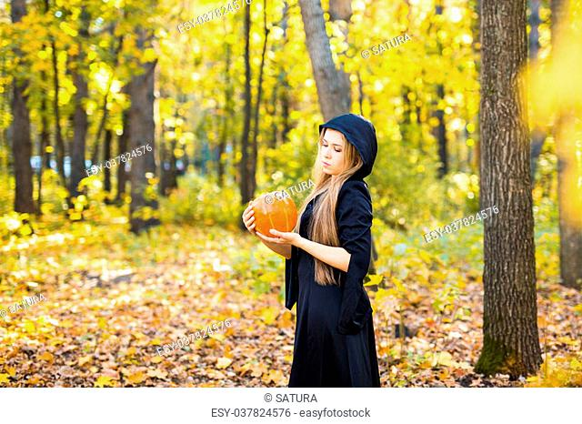 portrait of dramatic beautiful blond young woman holding pumpkin in forest. Halloween day