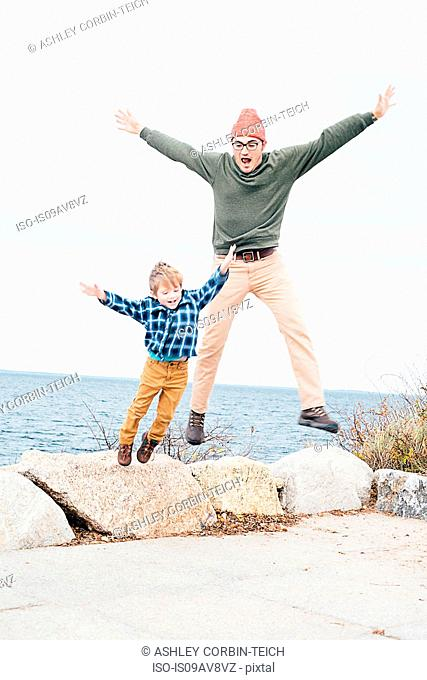 Father and son jumping off of rocks beside lake