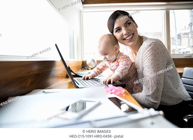 Mother and baby at laptop in home office